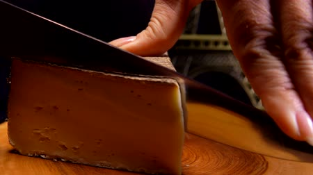 moldy : Knife cuts a thin slice of hard cheese on a wooden board against the background of the Eiffel Tower model