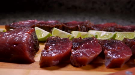atum : Close-up camera movement in pieces of lightly salted tuna and lime are lying on a bamboo cutting board