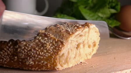 migalhas : Slow motion of crumbs fly from the knife cutting baguette with sesame seeds
