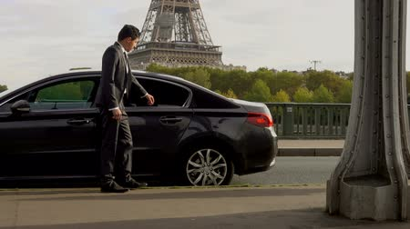 clique : Personal driver is opening the car door for his client next to the Eiffel Tower, hotel transfer services