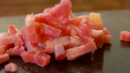 желток : Finely diced bacon falls on the surface of the stone grill