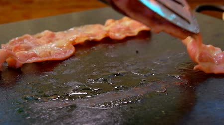 心のこもった : Cook turns bacon with metal tongs on the hot surface of the stone grill