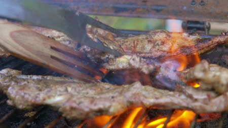 barbecued : Steak from lamb leg is turned over on a grill with two forks Stock Footage