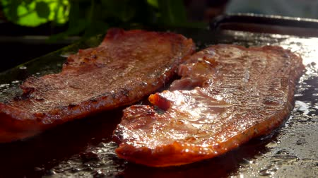бекон : Two strips of raw bacon are roasted on the hot stone surface of the grill