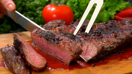 borrifar : Chef cuts the finished juicy beef steak on a wooden board with a large knife and fork Stock Footage