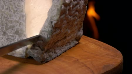 moldy : Piece of goat cheese with gray mold falls on the wooden board