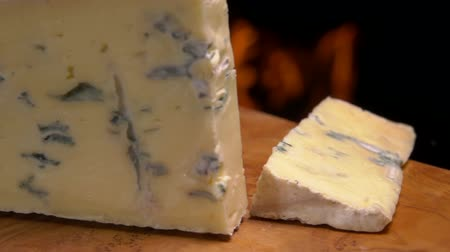 стартер : Cut piece of cheese with blue mold falls on a wooden board against the background of a burning fireplace