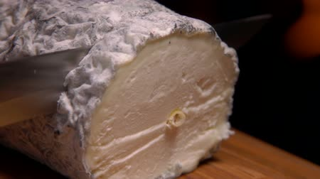 moldy : Natural goat cheese with gray mold is cut with a knife on a wooden board, close up
