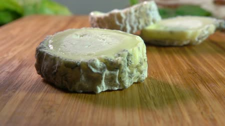 cheese piece : Piece of natural goat cheese with gray mold Le Sainte Maure falling on a wooden surface