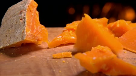 разница : Piece of Mimolett cheese falls on a wooden board against the background of a burning fireplace