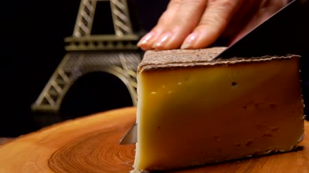 cheese piece : Knife cuts a thin slice of hard cheese on a wooden board against the background of the Eiffel Tower model
