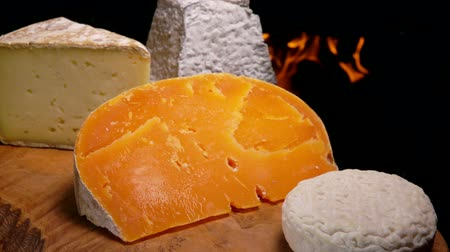 fig : Cut piece of cheese with blue mold falls on a wooden board against the background of a burning fireplace