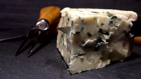 cheese slices : Knife cuts and lifts a piece of blue-mold cheese on a black stone board close up