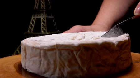 kalıp : Knife cuts off and pulls out a piece of Camembert cheese on a wooden board against the background of the Eiffel Tower model Stok Video