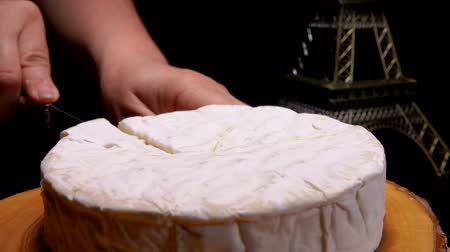 moldy : Knife cuts and pulls out a sector of Camembert cheese on a wooden board on the background of the Eiffel Tower model Stock Footage