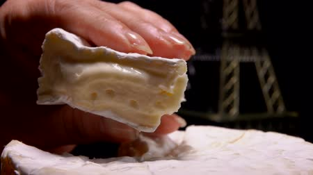 moldy : Fingers squeeze a sector of soft French cheese against the background of the Eiffel Tower model. Stock Footage