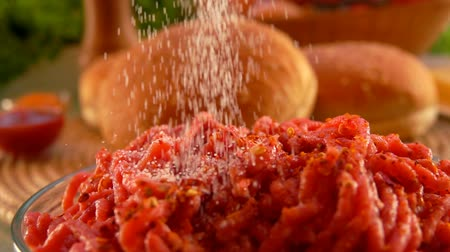 ground meat : Salt pour in ground beef to make hamburgers. On the table are cooked foods for hamburgers