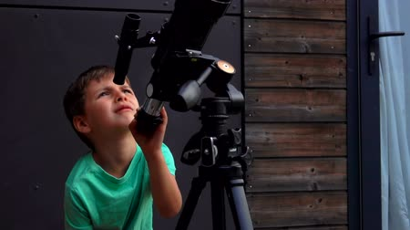 letec : Cheerful cute boy explores the sky through a telescope on a sunny summer day.