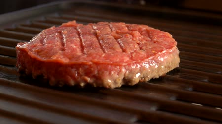 slanina : Smoke rises above the cutlet on a hot grill. Tasty beef burger flipping on the grill.