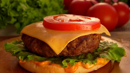 bacon burger : Round slice of tomato falls onto a piece of cheese on a hamburger. On the table are products for hamburgers Stock Footage