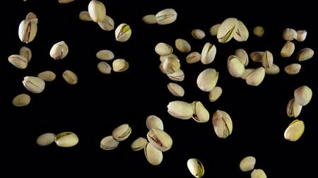 soyulmuş : Pistachios are flying on a black background in slow motion