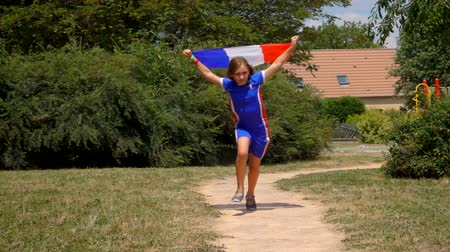 лига : Girl fan of the French national team runs for joy with a French flag in his hands.