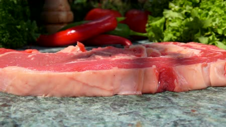 tomilho : Veal steak falls on a green marble table. Still life of meat, herbs, spices and vegetables Stock Footage
