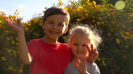 spolužák : Happy charming boy and girl waving their hands in the beam of sunlight