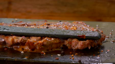 sürahi : Cook presses the steak on the hot surface of the stone grill with a spatula