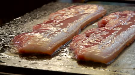 hátszín : Close-up camera movement near of a two strips of raw bacon are roasted on the hot stone surface of the grill