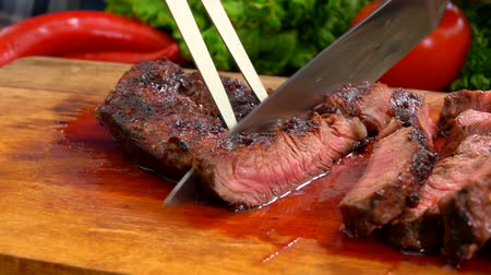 sürahi : Chef cuts the finished juicy beef steak on a wooden board with a large knife and fork Stok Video