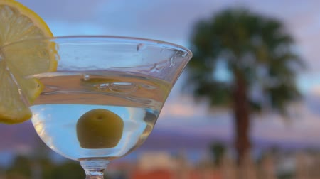 martini glasses : Olive falls into a glass with martini and lemon on a background of palm trees Stock Footage