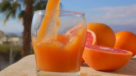 celý : Grapefruit juice is poured into a glass against the background of the sunny sea landscape, close-up camera motion