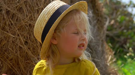 palheiro : Wind blows the hair of a little girl in a straw hat on a background of a haystack Stock Footage