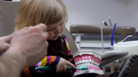 a medicare : Dentist doctor teaches a little girl to brush her teeth properly. Stock mozgókép