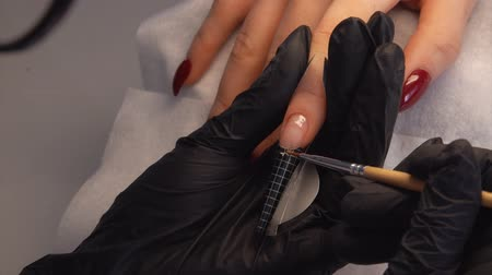 массаж : Manicurist produce nail extension with a special gel. Стоковые видеозаписи