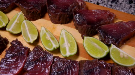 sardine : Slices of lightly salted tuna and lime are lying on a bamboo cutting board. Panoramic camera movement.