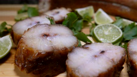 paling : Pieces of smoked eel and lime lie on a wooden board. Panoramic camera movement.