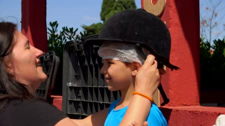 poník : Mom puts on a little boys head a black protective helmet for riding