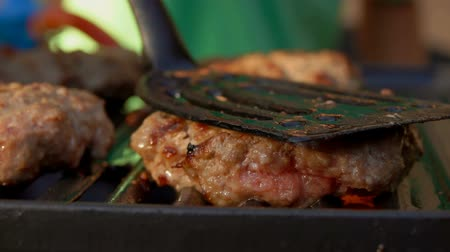 прессованный : Tasty beef burgers flipping on the grill. Burgers is pressed by kitchen spatula to the grill Стоковые видеозаписи