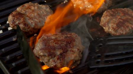hambúrguer : Tasty beef burgers flipping on the grill. Burgers is pressed by kitchen spatula to the grill Vídeos