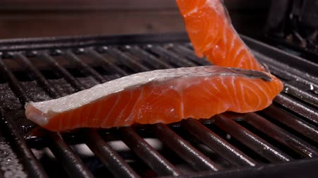 pisztráng : Cook puts the second piece of raw salmon fillet on the grill grate