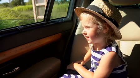 way out : Cheerful girl rides in the car and looks out the window on the road.