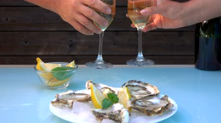 食用 : Male and female hand take glasses of champagne from a table over a plate of fresh open oysters on ice.