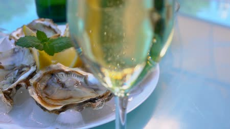 měkkýš : Bubbles of champagne rise to the top in a glass goblet on the background of a plate with oysters and lemon.