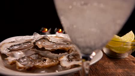osztriga : Champagne is poured into a glass on the background of a served table with fresh oysters on ice and candles