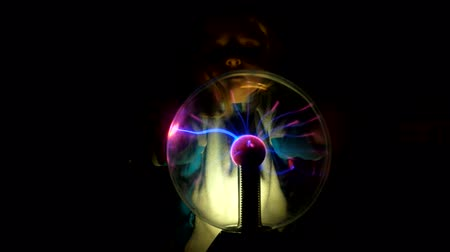 plasma : Pretty girl moves her fingers across the surface of the plasma ball and watches for changes in her condition