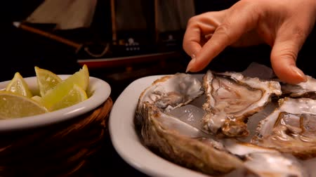 osztriga : Female hand takes fresh oysters on ice from the plate