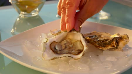 seafood dishes : Female hand puts open oysters on a plate with ice. Bowl of lemonsbowl of lemons