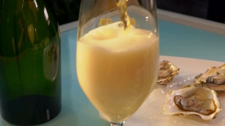 osztriga : Champagne is poured into a glass on the background of a plate with oysters on ice.